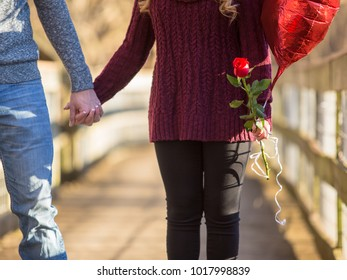 Attractive young couple facing the viewer holding hands she is holding a red rose and red heart shaped balloon torso only no faces
