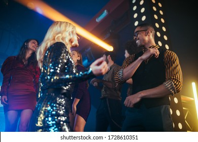 Un joli jeune couple qui s'amuse dans une discothèque