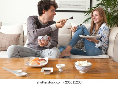 Attractive young couple having a night in at home and enjoying eating japanese take away food. Couple relaxing on home sofa eating exotic food with man offering food in a home interior.