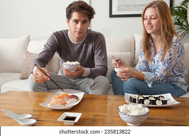 Attractive young couple having a night in at home and enjoying eating japanese take away food in each other's company. Couple relaxing on home sofa eating exotic food in a stylish home interior.