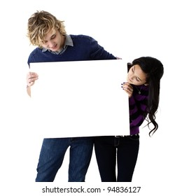 attractive young couple holding a blank sign