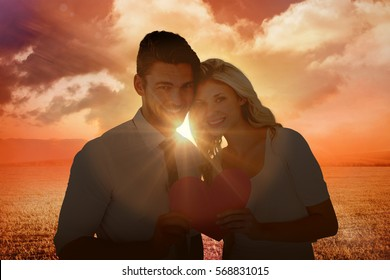 Attractive young couple holding pink heart against sunrise over field