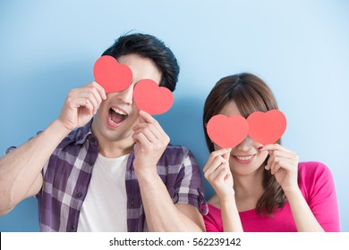 Attractive young couple holding red love hearts over eyes isolated on blue background