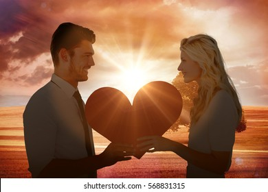 Attractive young couple holding red heart against sunrise over field with tree