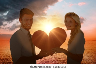 Attractive young couple holding red heart against sunrise over field
