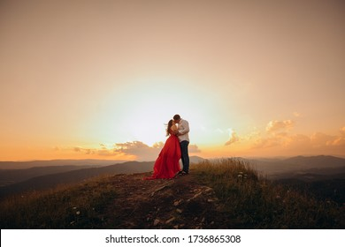 Attractive young couple kissing engaged in foreplay touching each other. Happy couple stands in embrace and kisses each other on beautiful sunset
