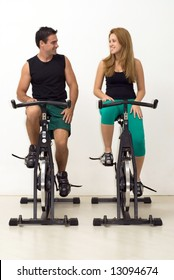 Attractive young couple looking at each other and smiling while working out on exercise bikes. Vertically framed, isolated shot.