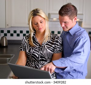 Attractive Young Couple Looking On A Laptop Computer In The Kitchen