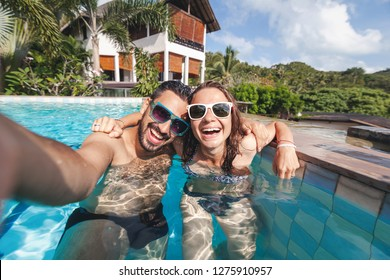 Attractive young couple in love is having fun in the outdoor pool, taking a selfie on a mobile phone; luxury luxury vacation, real estate in the tropics, honeymoon