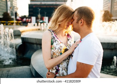 Attractive young couple lovely embracing and looking each other at city background in sunny day