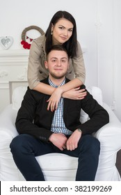 An attractive young couple. Maybe business style or a couple in love. A man sits on a chair beautiful girl embraces him.