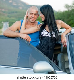 Attractive young couple near their car