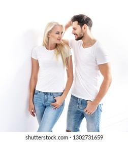 Attractive young couple posing in white room