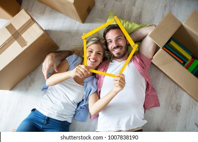 Attractive young couple relax between boxes on floor at new apartment, moving concept