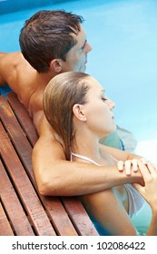 Attractive young couple relaxing together in swimming pool with blue water