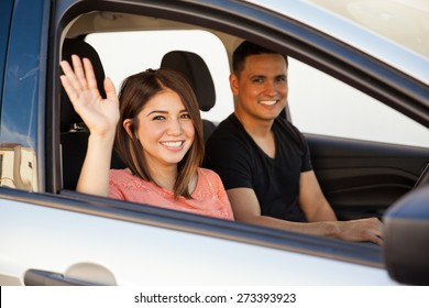 Attractive young couple saying goodbye before driving away in their car