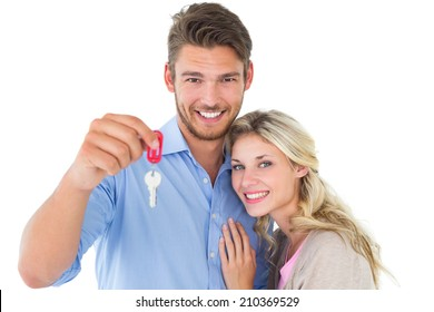 Attractive young couple showing new house key on white background