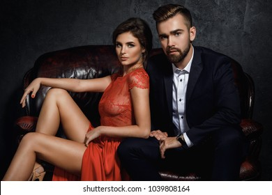 Attractive young couple is sitting on the leather sofa. Woman in red dress and man wearing classical suit.