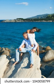 Attractive young couple sitting on the rocks on the beach. Sexy couple. Man and woman posing stone. Summer beach. Lifestyle, dream, dreaming. Travel concept. Happy day. Vacation. Happiness. Sensual.