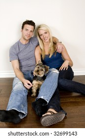 Attractive young couple sitting in their new home with their dog
