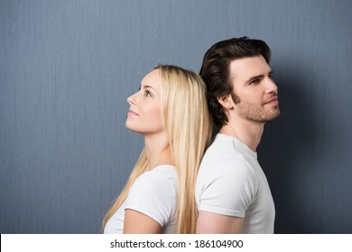 Attractive young couple standing back to back both staring thoughtfully into the distance with quiet smiles, on grey