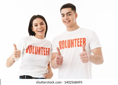 Attractive young couple standing isolated over white background, wearing volunteer t-shirts