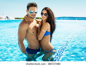 Attractive young couple in swimming pool wearing sunglasses and hugging at each other