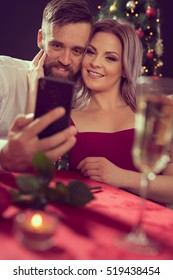 Attractive young couple taking a selfie while having a romantic dinner together