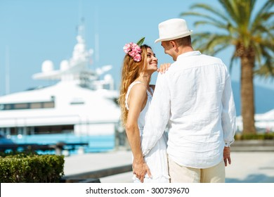 Attractive young couple walking alongside the marina with moored boats on a luxury waterfront in summer sunshine