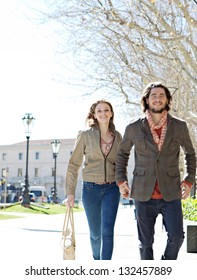 Attractive young couple walking fast together in a destination vacation city, holding hands and smiling.