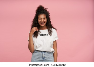 Attractive young curly long haired brunette female with dark skin touching her hair and looking positively to camera with charming smile, standing over pink background in casual clothes