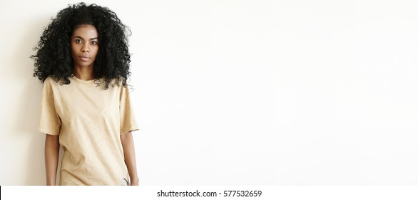 Attractive young dark-skinned woman with Afro hairstyle wearing oversize t-shirt looking at camera, having serious face expression. Cute African girl dressed casually posing indoors at white wall