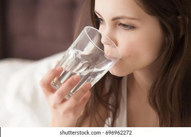 Attractive young dehydrated woman feeling thirsty, holding glass and drinking pure mineral water every morning after waking up, good habits for healthy way of life, dehydration concept, close up view