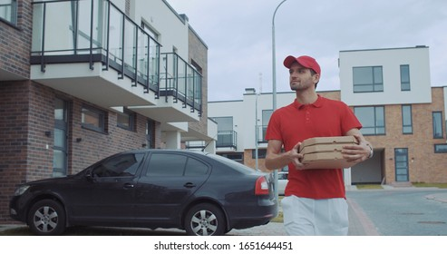 Attractive young delivery man in red uniform with hot pizza boxes walking in the street of modern neighbourhood to the customer house.