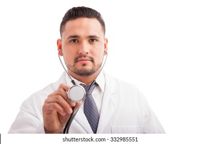Attractive young doctor with a beard using a stethoscope to examine a patient against a white background
