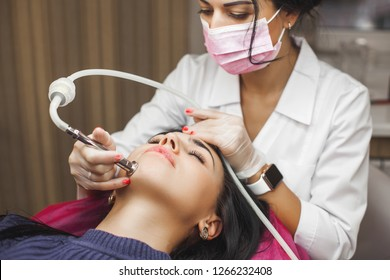 Attractive young doctor making mesotherapy to her client. Woman in the beauty salon. Doctor making face treatment with medical apparatus. Diamond skin peeling procedure in the clinic.