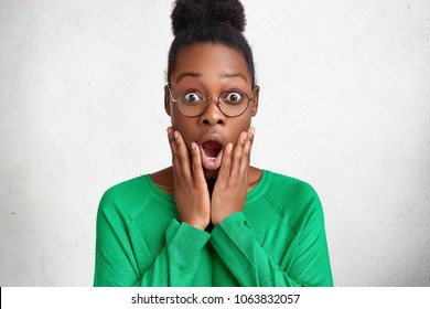 Attractive young emotional African American female looks with great surprisment at camera, keeps mouth widely opened, doesn`t expect to recieve money reward, isolated over white studio background
