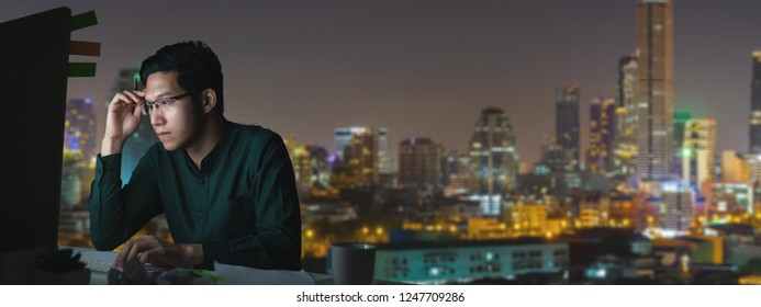 Attractive young engineer asian man or programmer sitting on desk table work late and hard with computer laptop at office with night light city view in noir concept smart worker with technology.