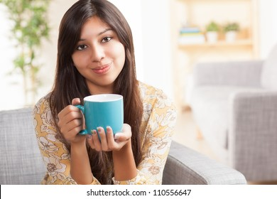 Attractive young ethnic woman in living room holding blue coffee mug wearing festive yellow shirt with flowers.