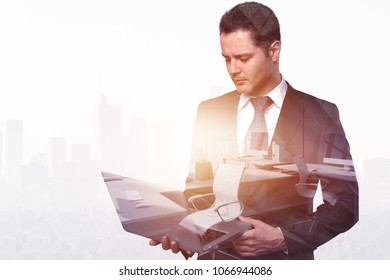 Attractive young european businessman using laptop on abstract city background with copy space. Technology and communication concept. Double exposure