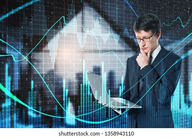 Attractive young european businessman using device with glowing forex chart in blurry office interior with binary code. Technology, network and trade concept. Double exposure