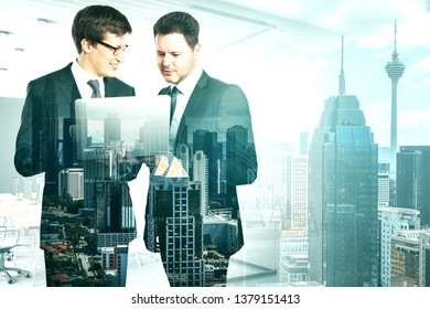 Attractive young european businessmen using laptop together on blurry office New York city interior background. Teamwork and network concept. Double exposure