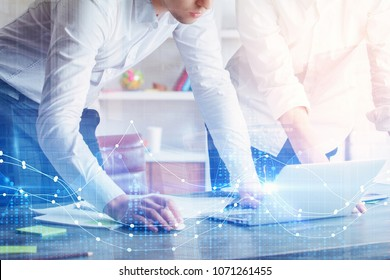 Attractive young european businesspeople using laptop with glowing forex graph on blurry office background. Investment, teamwork, future and trade concept. Double exposure