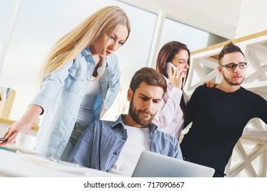 Attractive young european group, business men and women working on project in modern office with laptop, smartphone, paperwork and other items on desk. Brainstorm concept