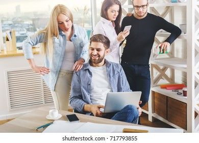Attractive young european group, business men and women working on project in modern office with laptop, smartphone, paperwork and other items on desk. Collaboration concept
