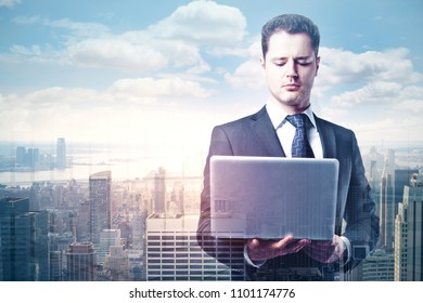 Attractive young european man using laptop on abstract city background. Technology and communication concept. Double exposure