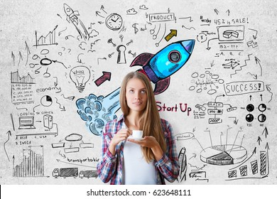 Attractive young european woman drinking coffee on concrete background with colorful launching rocket sketch. Entrepreneurship concept