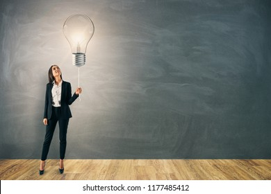 Attractive young european woman with glowing lightbulb balloon on chalkboard background. Idea and innovation concept