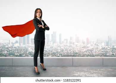 Attractive young european woman with red hero cape and folded arms standing on city background. Superhero and leader concept