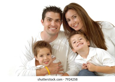 Attractive young family laughing while posing together for a portrait; copy space can be expanded